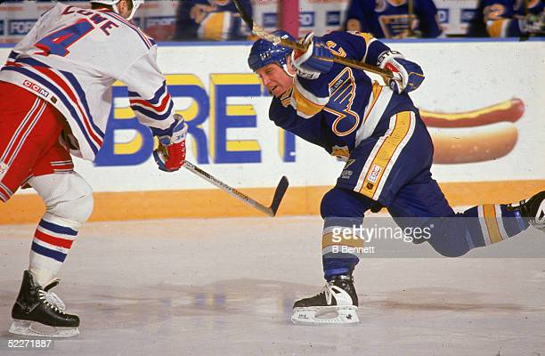 Canadian hockey player Brett Hull of the St Louis Blues fires off a shot as the New York Rangers' Kevin Lowe tries to stop him during a game at...