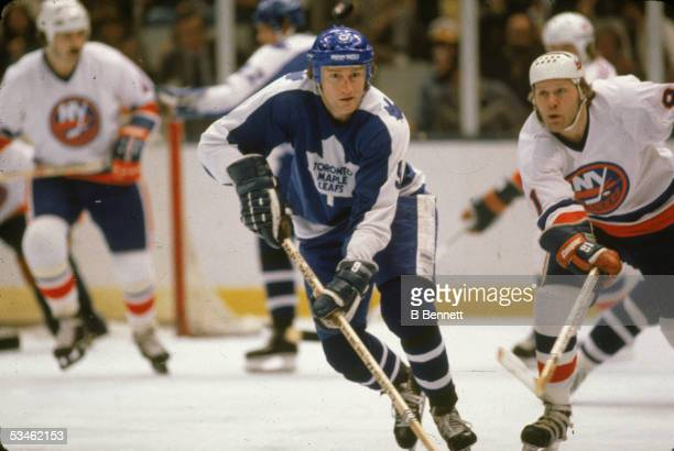 Canadian hockey player Dan Maloney of the Toronto Maple Leafs races for the puck with Butch Goring of the New York Islanders duiing a game at Nassau...