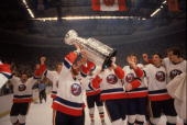 Canadian hockey player Denis Potvin captain of the New York Islanders and his teammates hoist the Stanley Cup in the air as the Islanders celebrate...