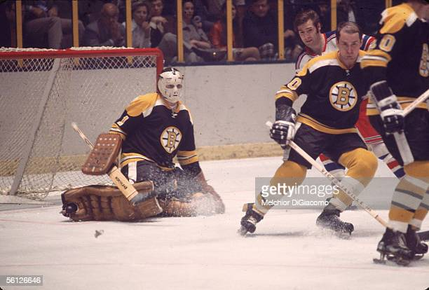 Canadian hockey player Ed Johnston goalie of the Boston Bruins defends his goal as other players including Bill Fairbairn of the Rangers and Dallas...