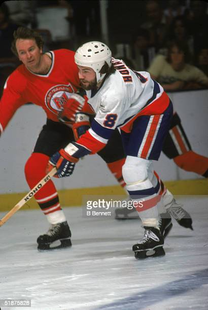 Canadian hockey player Gary Howatt of the New York Islanders reaches past Walt McKechrie of the Cleveland Barons during a game at Nassau Coliseum...