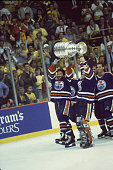 Canadian hockey player Glenn Anderson of the Edmonton Oilers and his teammates celebrate by skating around the rink with the Stanley Cup held aloft...