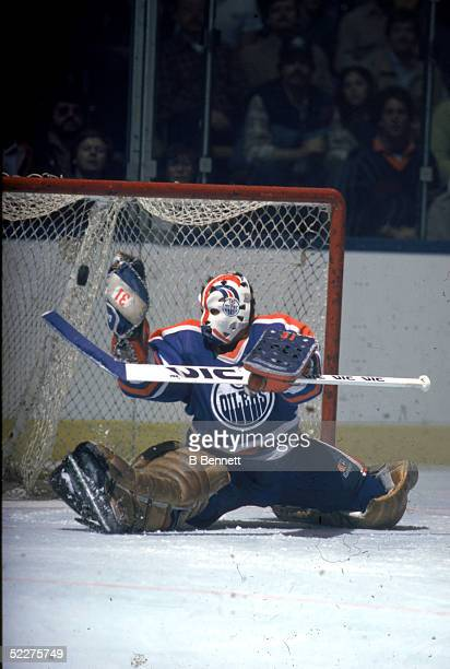 Canadian hockey player Grant Fuhr goalkeeper for the Edmonton Oilers makes a save during a road game at the Nassau Coliseum Uniondale New York 1980s