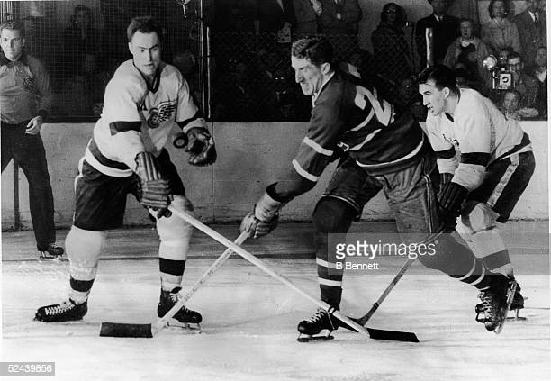 Canadian hockey player Red Kelly of the Detroit Red Wings battles with Paul Masnick of the Montreal Canadiens for an airborne puck while Red Wing...