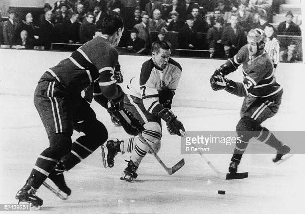 Canadian hockey player Tim Horton of the Toronto Maple Leafs skates between Jacques Laperriere and Jean Claude Trembly both of the Montreal Canadiens...