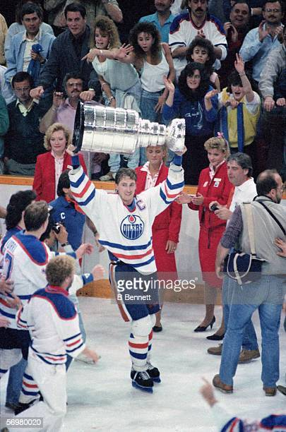 Canadian hockey player Wayne Gretzky of the Edmonton Oilers raises the Stanley Cup over his head in victory after the Oilers defeated the...