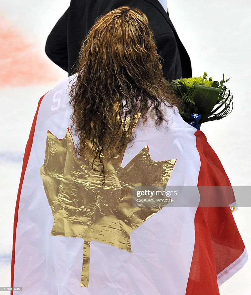 A Canadian hockey player wears the national flag with a golden Maple leaf during the medals ceremony in the Woman's Ice Hockey games at the Canada Hockey Place during the XXI Winter Olympic Games in Vancouver, Canada on February 25, 2010. Canada beat the USA 2-0 to win the gold and Finland beat Sweden 3-2 to win the bronze.