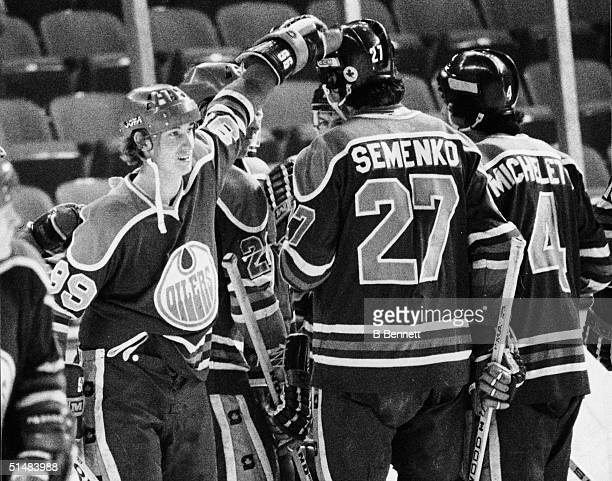 Canadian hockey players Wayne Gretzky #99 for the Edmonton Oilers and Dave Semenko celebrate a win with American teammate Joe Micheletti after a...