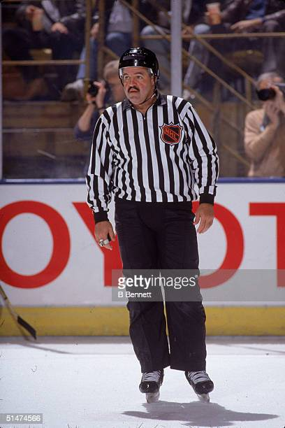 Canadian ice hockey linesman Rod Asselstine watches game play while photographers behind him capture the action 1980s