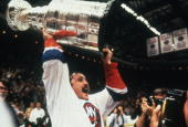 Canadian ice hockey player Bryan Trottier of the New York Islanders shouts triumphanly as he holds aloft the Stanley Cup in celebration of his team's...