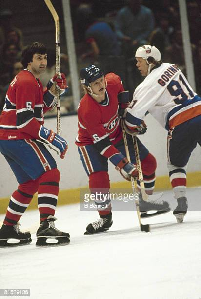 Canadian ice hockey player Butch Goring of the New York Islanders tries to block Pierre Mondou and Guy Lapointe of the Montreal Canadiens during a...
