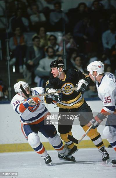 Canadian ice hockey player Cam Neely of the Boston Bruins fights for position with Bryan Trottier of the New York Islanders during a game at the...