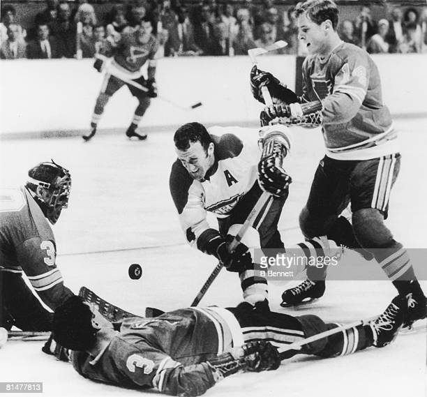 Canadian ice hockey player Claude Provost tooks for the puck amid downed St Louis Blues players Al Arbour and goalie Jacques Plante while the Blues'...