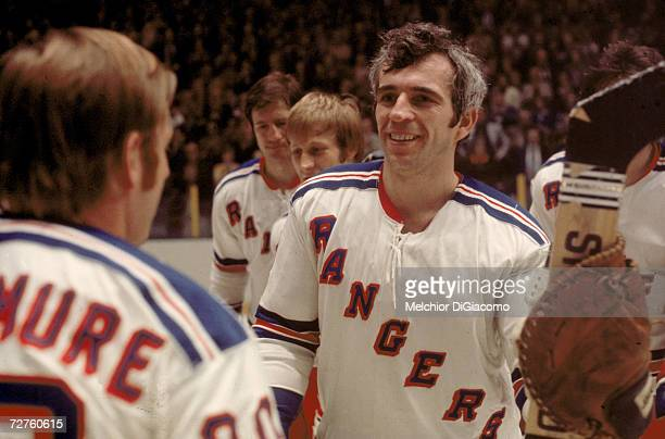 Canadian ice hockey player Ed Giacomin goalkeeper for the New York Rangers smiles as he talks with teammates on the ice early to mid 1970s