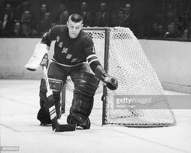 Canadian ice hockey player Gump Worsley goalkeeper for the New York Rangers reaches for an airborne hockey puck during a game 1950s or early 1960s