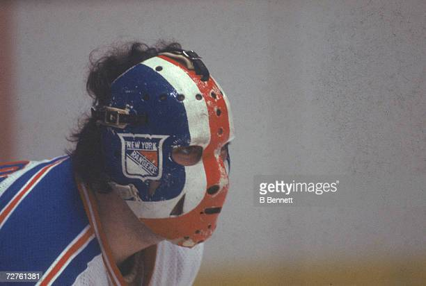 Canadian ice hockey player John Davidson goalkeeper for the New York Rangers keeps an eye on the action during a game late 1970s His facemask is...