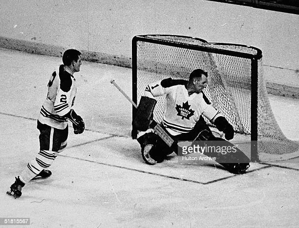 Canadian ice hockey player Johnny Bower of the Toronto Maple Leafs minds the net as fellow Leaf Larry Hillman skates back to help out during the...