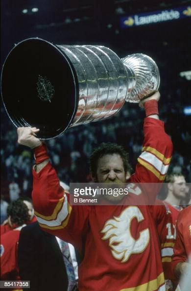 Canadian ice hockey player Lanny McDonald of the Calgary Flames yells triumphantly as he holds the Stanley Cup trophy aloft after his team's victory...