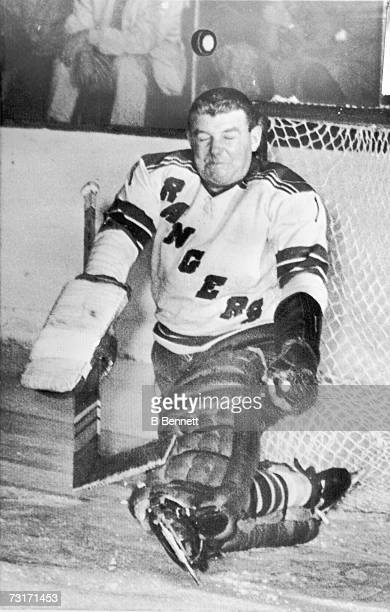 Canadian ice hockey player Lorne 'Gump' Worsley goalkeeper for the New York Rangers makes a face as a hockey bounces off his head during a game...