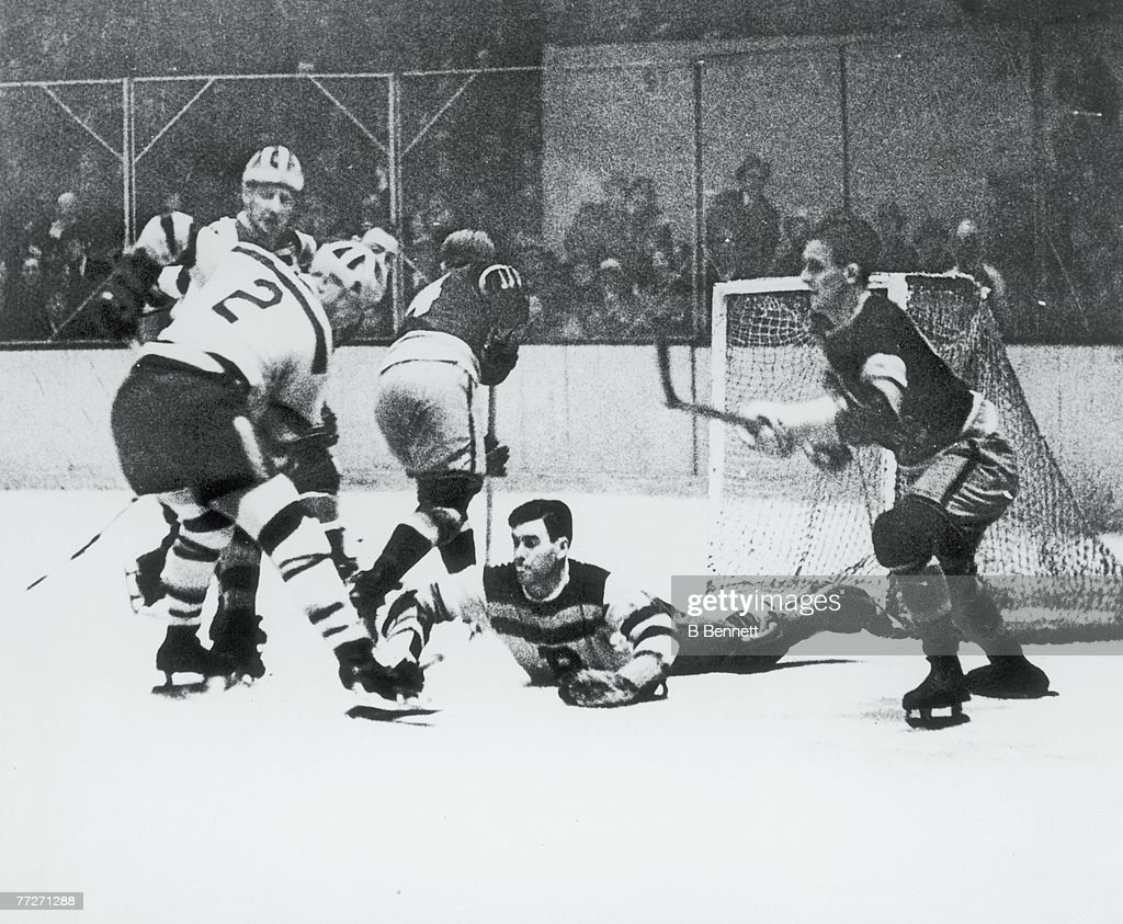 Canadian ice hockey player Tiny Thompson goalkeeper for the Boston Bruins reaches to make a save while his teammates including Eddie Shore try to...