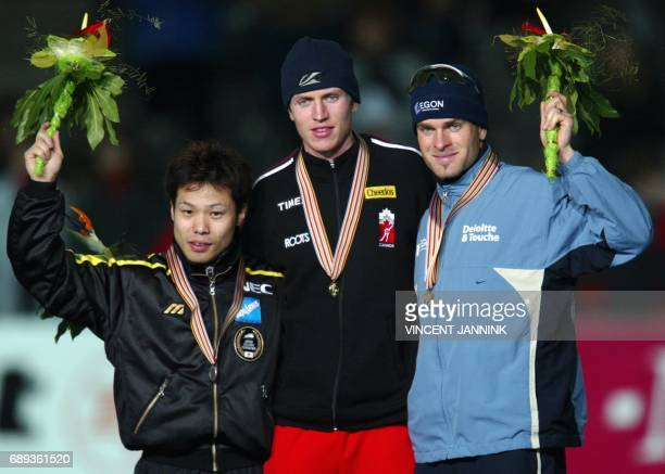 Canadian Jeremy Wotherspoon Hiroyasu Shimizu of Japan and Erben Wenners of the Netherlands cheer on the podium 14 March 2003 after the speed skating...