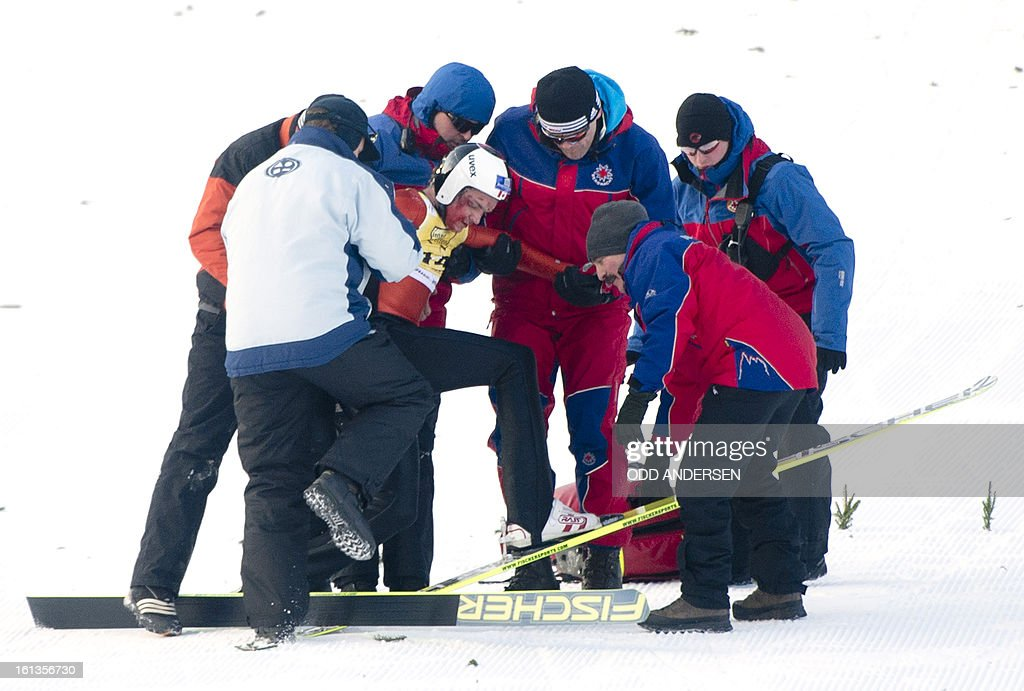 Canadian jumper MacKenzie Boyd-Clowes is helped up after crashing during a show jump after the cancellation of the FIS Ski Jumping World Cup individual large hill competition on the Muehlenkopfschanze hill in Willingen, western Germany on February 10, 2013.