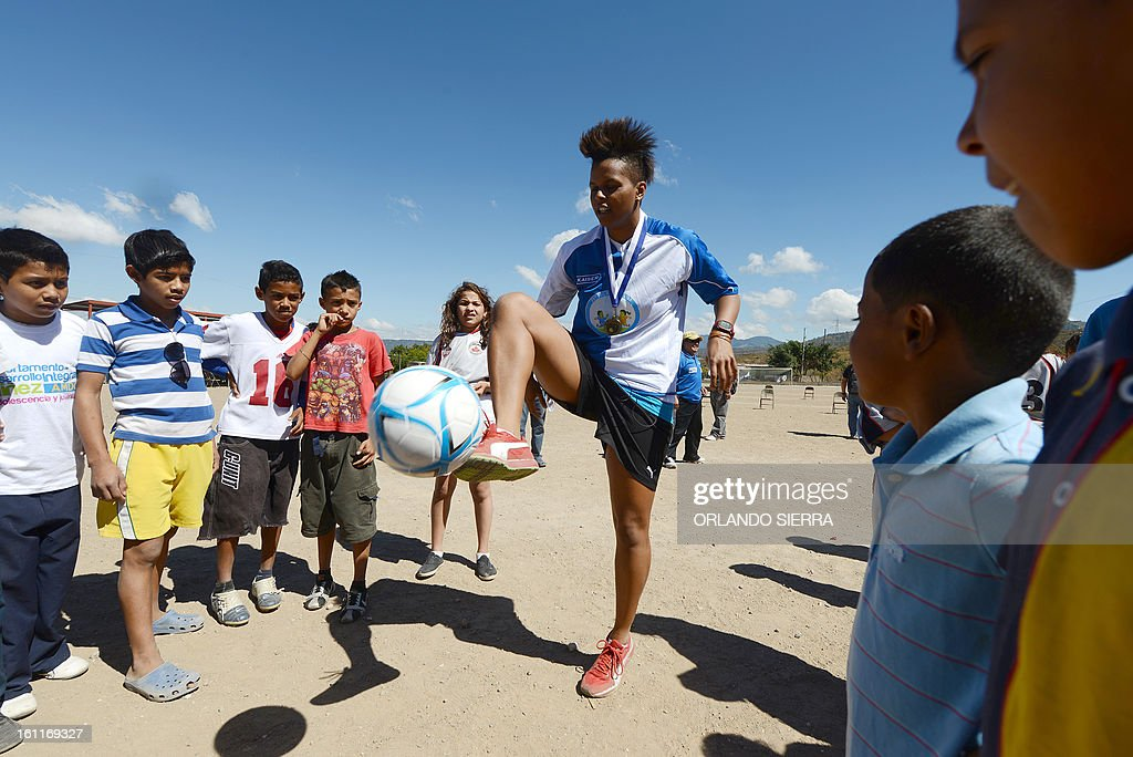 Canadian Karina LeBlanc (C), UNICEF goodwill ambassador, teach football techniques to children from low-income families in Tegucigalpa, on February 9, 2013. LeBlanc, the Canadian female football team goalkeeper, visited Honduras to encourage the practice of sports creating a safe environment for children as a way to prevent mistreatment and abuse. AFP PHOTO/Orlando SIERRA