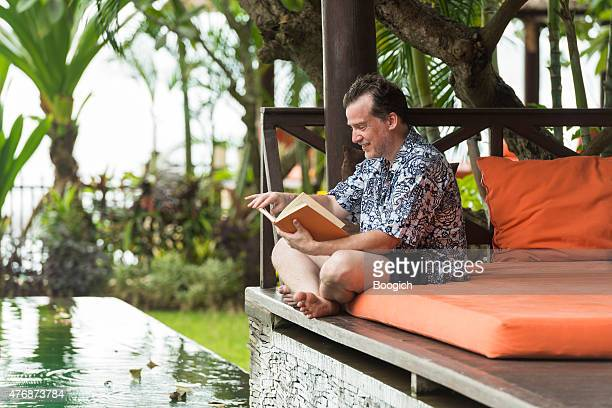 Canadian Man Reading Poolside on Summer Vacation in Bali Cabana