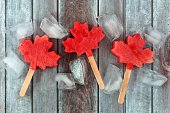 Canadian maple leaf watermelon pops with ice cubes on a rustic aged wood background