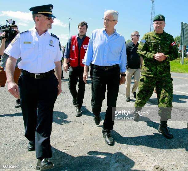 Canadian Minister of Transport Marc Garneau center walks with military officers before touring the migrant camp at St Bernard de Lacolle Among the...