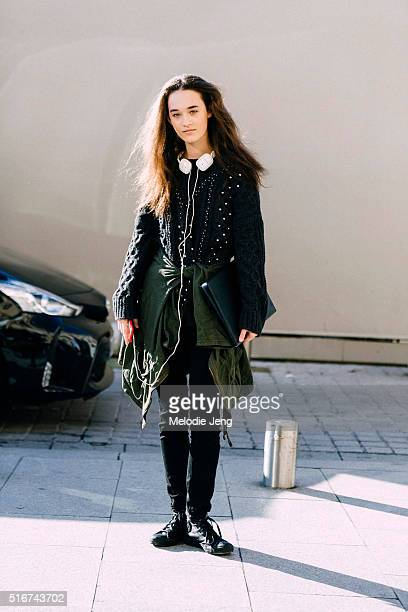 Canadian model Elizabeth Davison wears crimped hair white headphones and a jacket around her waist after the Schiaparelli Couture show at Place...