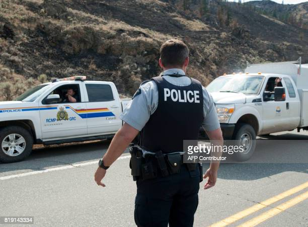 Canadian Mounted Police block traffic from going on highway 97 north of Cache Creek BC July 19 2017 as forest fires rage in western Canada The...