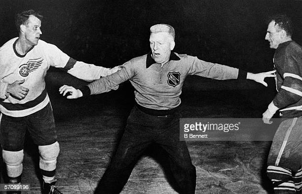 Canadian NHL referee and former professional football player Red Storey gets in between Canadian professional hockey players Gordie Howe of the...