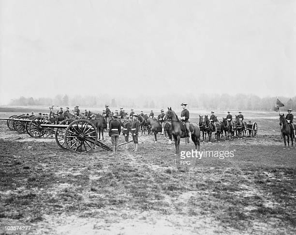 Canadian officers on horseback and standing by a row of cannons Canada circa 1890