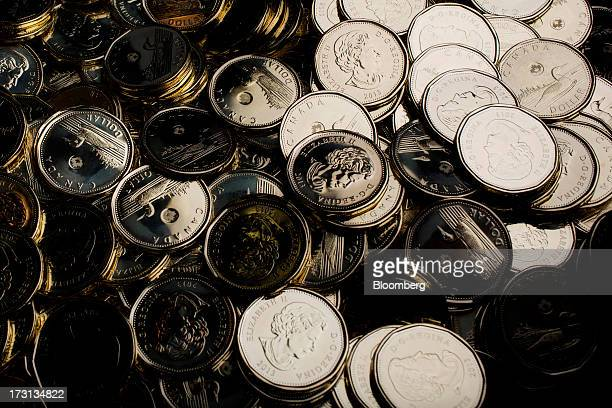 Canadian one dollar coins also known as Loonies sit in a pile at the Royal Canadian Mint in Winnipeg Ontario Canada on Friday July 5 2013 The...