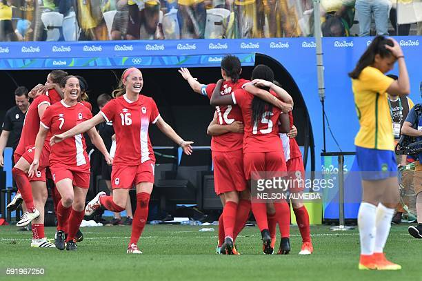 TOPSHOT Canadian players celebrate after their team's victory in their women's bronze medal football match between Brazil vs Canada at the Arena...