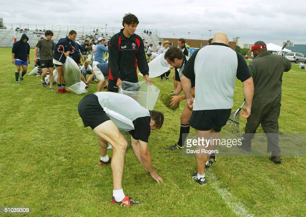 Canadian players clear the pitch of grass cuttings prior to the Canadian Rugby Union training held at York Stadium on July 9 2004 in Toronto Canada