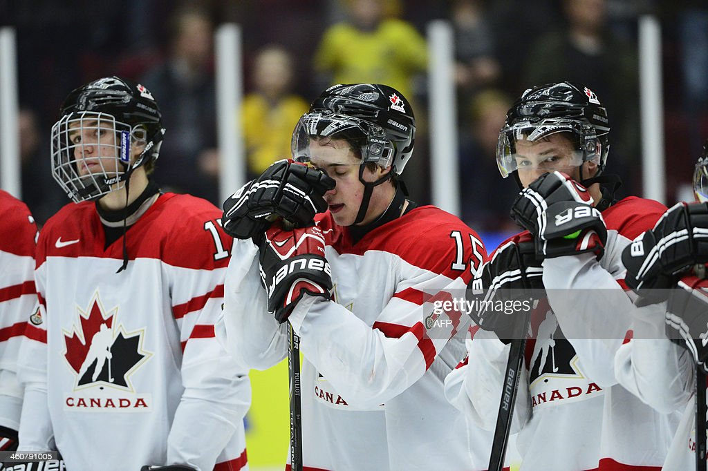 Canadian players with Derrick Pouliot (C) react after being defeated at the World Junior Ice Hockey Championships bronze match against Russia at Malmo Arena in Malmo, Sweden on January 5, 2014. Russia won 2-1.