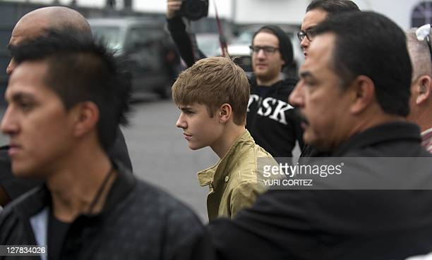 Canadian pop singer Justin Bieber is escorted by bodyguards during a photo opportunity before his concert as part of his 'My World Tour' at the Foro...