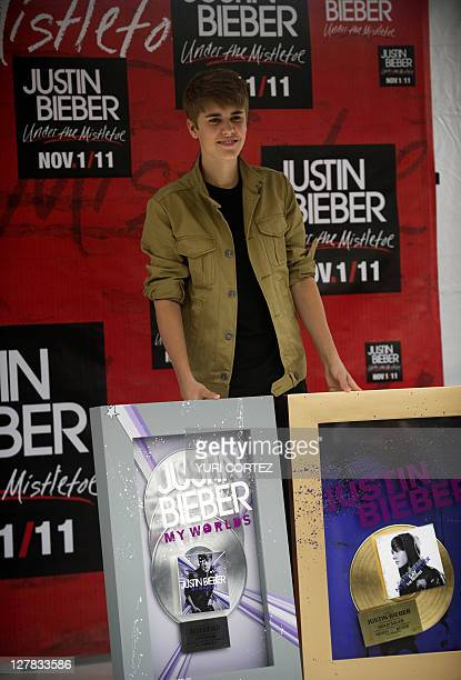 Canadian pop singer Justin Bieber poses with his platinum and gold discs during a photo opportunity before his concert as part of his 'My World Tour'...