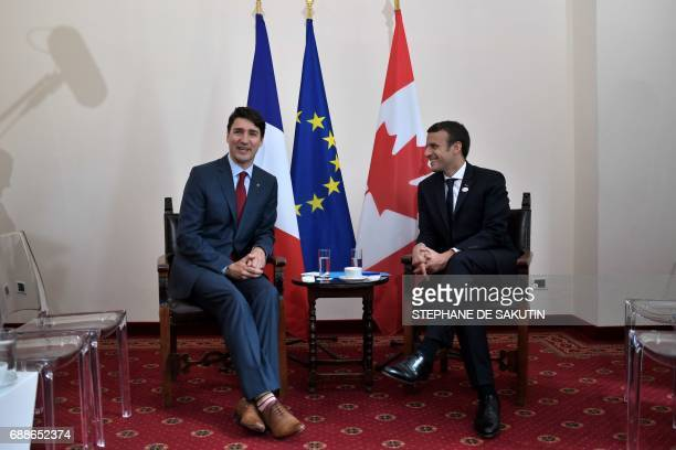 Canadian Prime Minister Justin Trudeau and French President Emmanuel Macron share a smile during a bilateral meeting as they attend the Summit of the...