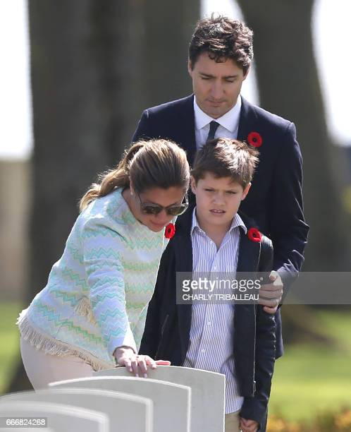 Canadian Prime Minister Justin Trudeau his wife Sophie Gregoire and their son Xavier look at the headstone of a member of Mrs Trudeau's family who...