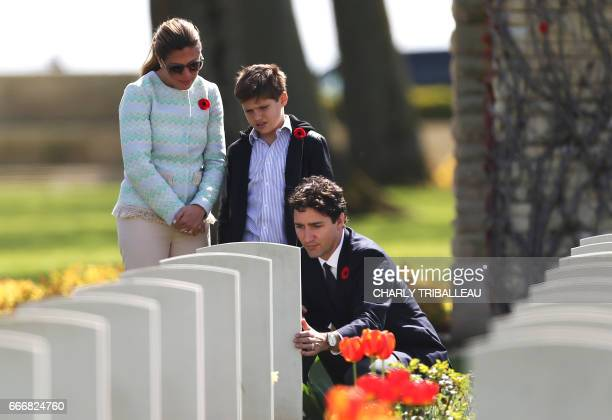 Canadian Prime Minister Justin Trudeau his wife Sophie Gregoire and their son Xavier stand in front of the headstone of a member of Mrs Trudeau's...