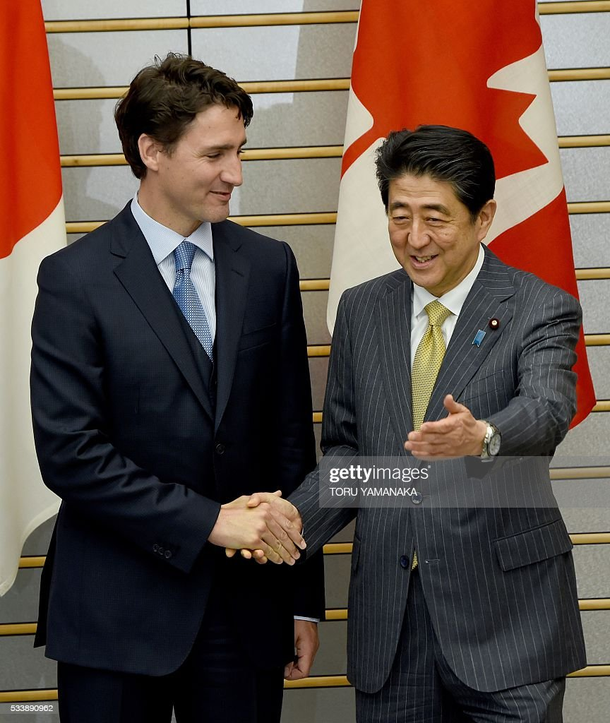 Canadian Prime Minister Justin Trudeau (L) is led by his Japanese counterpart Shinzo Abe (R) prior to their talks at Abe's official residence in Tokyo on May 24, 2016. Trudeau is here to attend the summit meeting of the Group of Seven in Ise-Shima, a place seen by many as Japan's spiritual home. / AFP / POOL / TORU