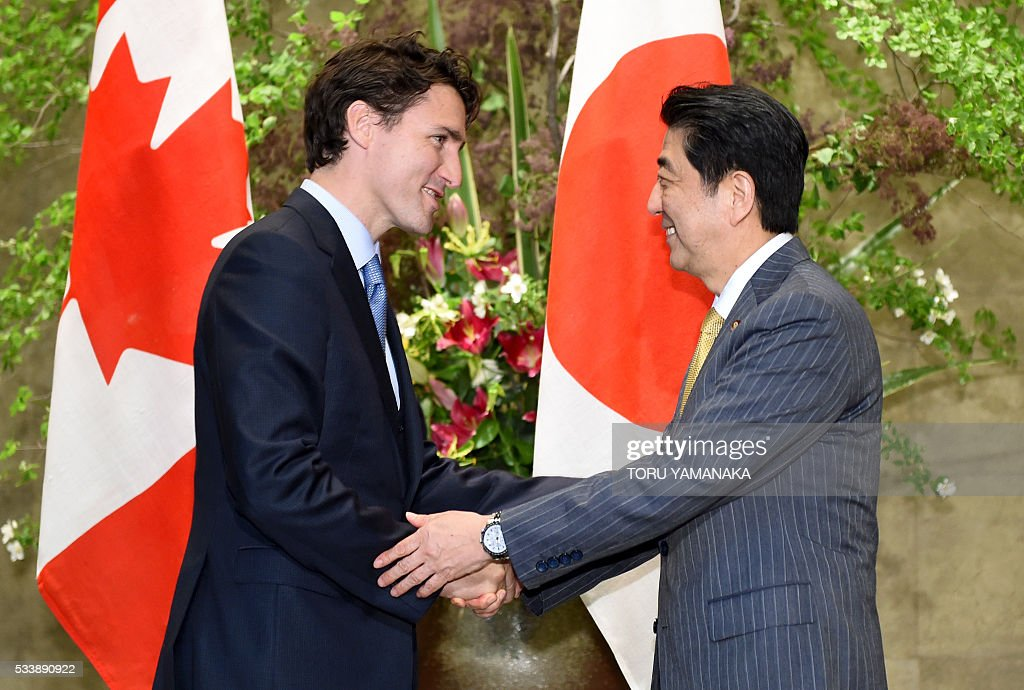 Canadian Prime Minister Justin Trudeau (L) is welcomed by his Japanese counterpart Shinzo Abe (R) upon his arrival at Abe's official residence in Tokyo on May 24, 2016. Trudeau is here to attend the summit meeting of the Group of Seven in Ise-Shima, a place seen by many as Japan's spiritual home. / AFP / POOL / TORU