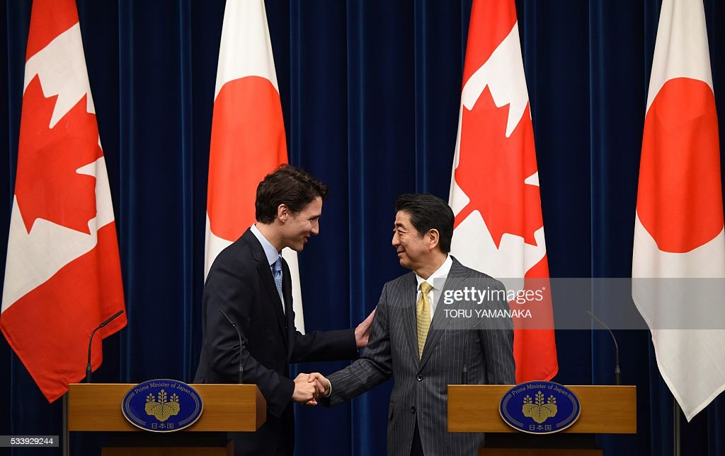 Canadian Prime Minister Justin Trudeau (L) shakes hands with his Japanese counterpart Shinzo Abe (R) after they speak at jounalists at Abe's official residence in Tokyo on May 24, 2016. Trudeau is here to attend the summit meeting of the Group of Seven in Ise-Shima, a place seen by many as Japan's spiritual home. / AFP / POOL / TORU