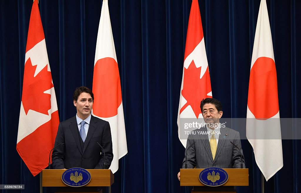 Canadian Prime Minister Justin Trudeau (L) speaks at jounalists after his talks with his Japanese counterpart Shinzo Abe (R) at Abe's official residence in Tokyo on May 24, 2016. Trudeau is here to attend the summit meeting of the Group of Seven in Ise-Shima, a place seen by many as Japan's spiritual home. / AFP / POOL / TORU