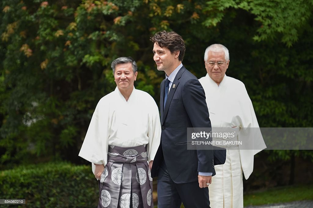 Canadian Prime Minister Justin Trudeau (C) walks past Shinto priests as he arrives at Ise-Jingu Shrine in the city of Ise in Mie prefecture, on May 26, 2016 on the first day of the G7 leaders summit. World leaders kick off two days of G7 talks in Japan on May 26 with the creaky global economy, terrorism, refugees, China's controversial maritime claims, and a possible Brexit headlining their packed agenda. / AFP / STEPHANE