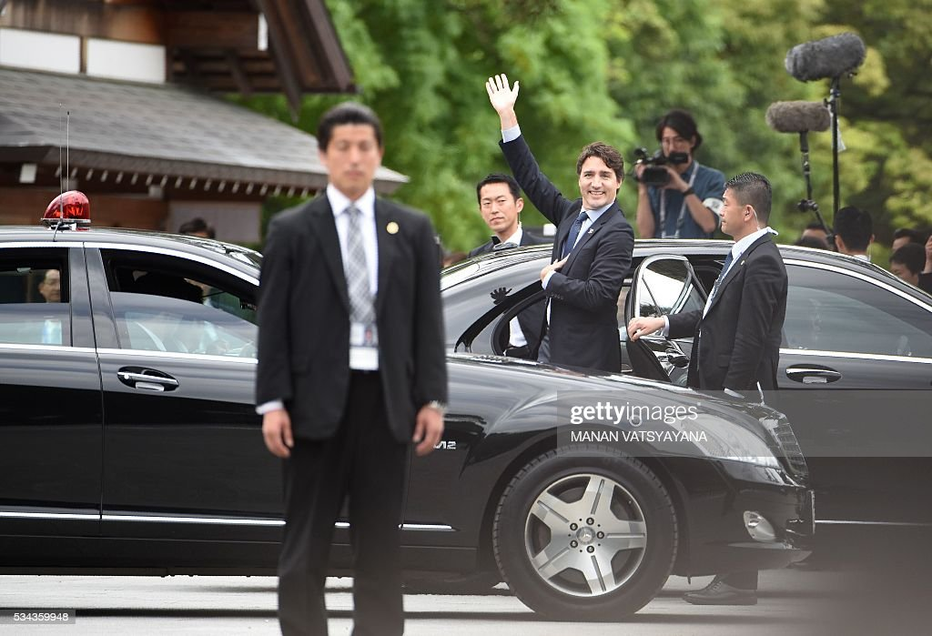 Canadian Prime Minister Justin Trudeau (C) waves upon his arrival at Ise-Jingu Shrine in the city of Ise in Mie prefecture, on May 26, 2016 on the first day of the G7 leaders summit. World leaders kick off two days of G7 talks in Japan on May 26 with the creaky global economy, terrorism, refugees, China's controversial maritime claims, and a possible Brexit headlining their packed agenda. / AFP / Manan VATSYAYANA
