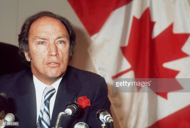 Canadian Prime Minister Pierre Elliott Trudeau wearing a rose in his buttonhole addresses media 23 October 1974 in Paris in front of a Canadian flag...
